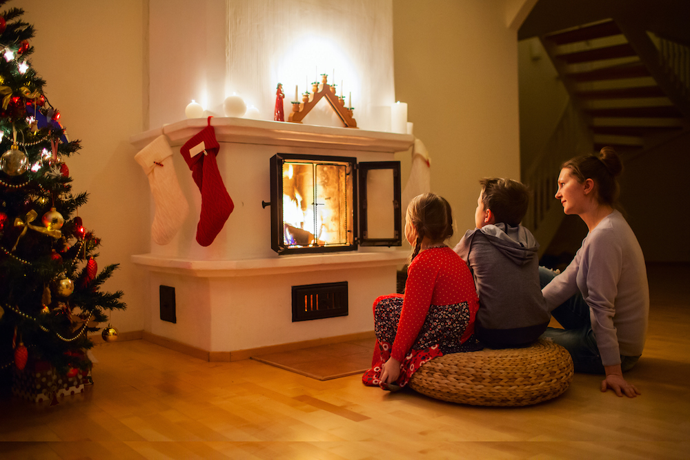 Family of mother and her two little kids sitting by a fireplace in their family home on Christmas eve